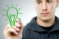 Man draws a green bulb Royalty Free Stock Photography