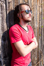 Man with dreadlocks enjoying morning sun in front an old wooden shack Stock Images