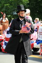 Man dressed in the likeness of abe lincoln in parade saratoga springs ny tall period clothing and abraham marching and handing out Royalty Free Stock Image