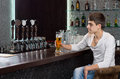 Man drinking beer alone on a pub attractive young sitting at counter pint of draught as he waits for his friends to arrive Stock Images