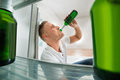 Man Drinking Beer In Front Of Open Refrigerator Royalty Free Stock Photo