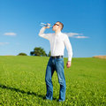Man drinking bottled water in a field casual young standing green under blue sky quenching his thirst Stock Photo