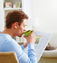 Man drinking coffee and reading newspaper Stock Image