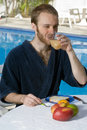 Man Drinking Juice Next to a Pool - Vertical Stock Image