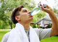 Man drinks the young water from a bottle Stock Images