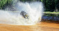 Man driving ATV quad through splashing water with high speed. Royalty Free Stock Photo