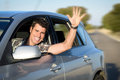 Man driving car on road in and waving male driver having fun traveling trip Stock Photo