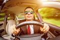 Man driving a car in suit and sunglasses on road in the Stock Photos