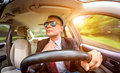 Man driving a car in suit and sunglasses on road in the Royalty Free Stock Photos