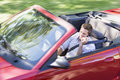 Man driving convertible car using cellular phone Royalty Free Stock Image