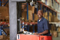 Man driving fork lift truck in warehouse smiling to camera Royalty Free Stock Photo