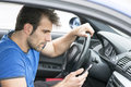 Man driving and looking message in his smart phone Royalty Free Stock Photo