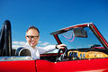 Man driving a vintage cabriolet with the hood down turning to smile at the camera blue sky background Royalty Free Stock Images