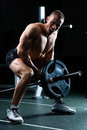 Man at dumbbell training in gym strong bodybuilder with dumbbells a exercising with a barbell Royalty Free Stock Image