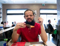 Man eating his meal at a Japanese restaurant and making funny face at a piece of salmon Royalty Free Stock Photo