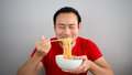 Man eating instant noodles.