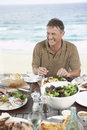 Man eating meal near the sea cheerful middle aged Stock Photo