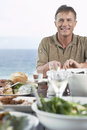 Man eating meal near the sea smiling middle aged Royalty Free Stock Photos