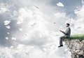 Man on edge reading book and paper planes flying in air Royalty Free Stock Photo