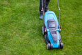 Man with an electric mower on green grass