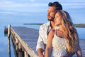 Man embracing his woman from behind on seaside background under Royalty Free Stock Photo