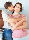 Man embracing and kissing a woman in the kitchen Stock Photography