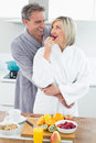 Man embracing a woman from behind in kitchen happy women the at home Royalty Free Stock Photo
