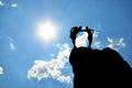 Man en vrouw die zich op een klip bevinden die tegen de zonnige hemel koesteren Stock Fotografie