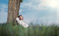 Man enjoy in music sideways profile of young listen repose grass guy leaning against a tree relaxing resting outdoors outside Stock Photography