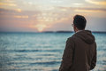 Man enjoying sunset over the sea unrecognizable young beautiful rear view space for text in left part of image Stock Photo