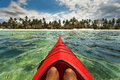 Man enjoying time in a kayak view from inside on ocean with beac