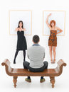 Man entertained by two women in an art gallery happy leaning angaist a white wall with empty frames front of a men sitting on a Stock Image