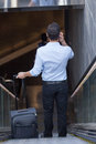 Man on escalator calling using the talking phone from behind Royalty Free Stock Images