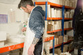 Man evens plaster on mold using a paintbrush in splattered clothing and apron levels the surface of fresh mixture Royalty Free Stock Photography