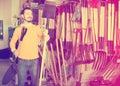 Man examines shovel options Royalty Free Stock Photo
