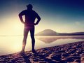 Man exercising on beach.  Silhouette of active man exercising  and stretching at lake Royalty Free Stock Photo