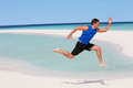 Man exercising on beautiful beach leaping Stock Image