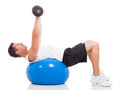 Man exercising dumbbells healthy young using a fitness ball and on white background Stock Photography