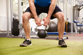 Man exercising in a gym with a kettlebell weight, crop Royalty Free Stock Photo