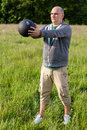 Man exercising with kilos medicine ball outdoors he is doing sport Royalty Free Stock Images