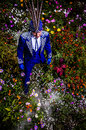 Man in expensive dark blue suit of illusionist pose on flower meadow photo Stock Photos