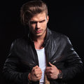 Man expressing his anger and pulling his leather jacket young fashion on dark background Royalty Free Stock Images