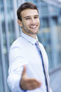 Man extending his hand for a handshake portrait of young business smiling Royalty Free Stock Images