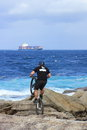 Man extreme biking on rocky shore a trains his skills the with a cargo ship in the background Royalty Free Stock Photography