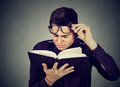 Man with eye glasses trying to read book has sight problems Royalty Free Stock Photo