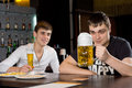 Man eyeing a large tankard of beer in anticipation as he sits with friend enjoying an evening out together at the pub Stock Image