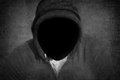 Man without a face mystery or death concept black hood with black grunge scratched background Stock Images