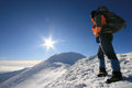 Man facing the sun hiking on crests of fagaras mountains in winter time Stock Photos
