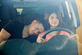 Man falling asleep on a trip portrait of beautiful young women driving car while her boyfriend falls her shoulder Stock Photo