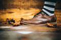 Man fashion brown shoe on wood background with striped socks Royalty Free Stock Photo